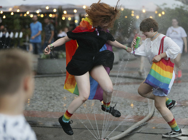 People take part in a gay pride parade in Warsaw, Poland, on Saturday, June 8, 2019. The Equality Parade is the largest gay pride parade in central and Eastern Europe. It brought thousands of people to the streets of Warsaw at a time when the LGBT rights movement in Poland is targeted by hate speeches and a government campaign depicting it as a threat to families and society. (Photo by Czarek Sokolowski/AP Photo)