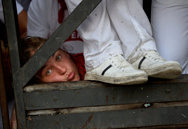 A reveler looks through the barrier before the second running of the bulls at the San Fermin festival in Pamplona, northern Spain, July 8, 2017. (Photo by Eloy Alonso/Reuters)