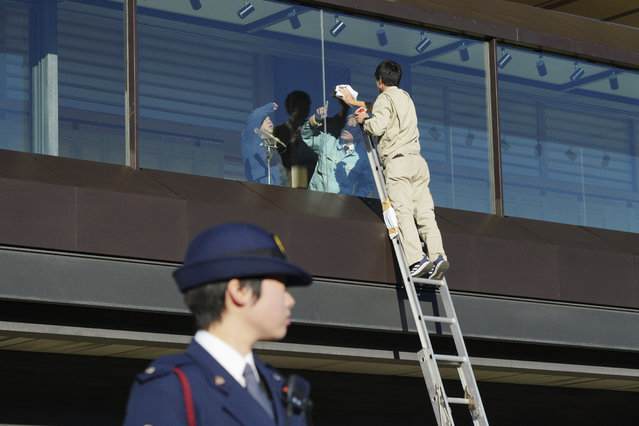 Workers clean the bullet-proofed balcony prior to Japan's Emperor Naruhito's public appearance with his imperial families at Imperial Palace in Tokyo Thursday, January 2, 2020. (Photo by Eugene Hoshiko/AP Photo)