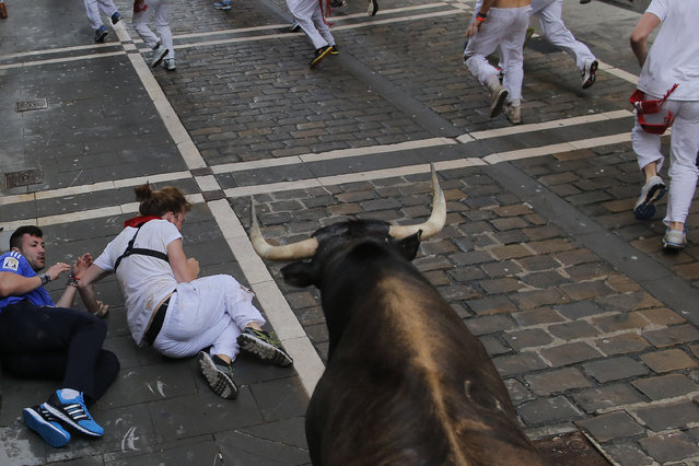 Revelers fall as a Dolores Aguirre fighting bull runs during the running of the bulls of the San Fermin festival, in Pamplona, Spain, Tuesday, July 8, 2014. (Photo by Andres Kudacki/AP Photo)