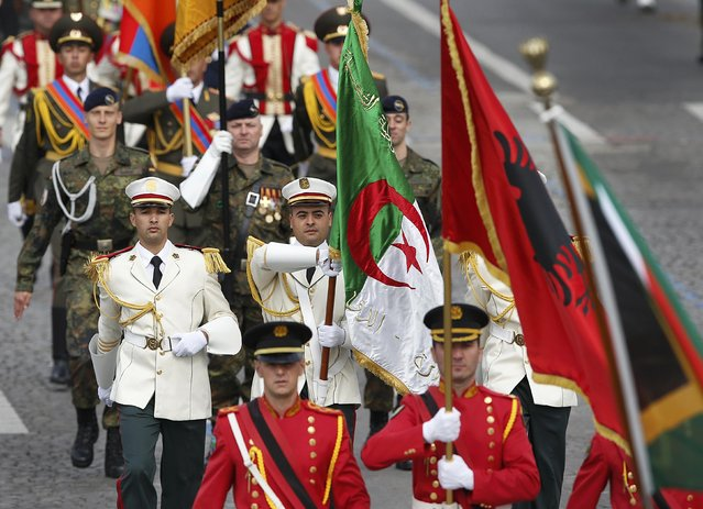 The Algerian flag is carried by parade participants in Paris, on Jule 14, 2014. (Photo by Benoit Tessier/Reuters)