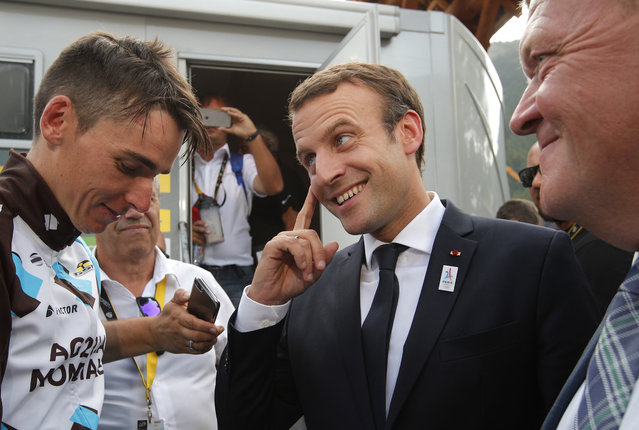 French President Emmanuel Macron, center, talks to France's Romain Bardet as Danish Prime Minister Lars Lokke Rasmussen, right, looks on, after the seventeenth stage of the Tour de France cycling race over 183 kilometers (113.7 miles) with start in La Mure and finish in Serre-Chevalier, French Alps, Wednesday, July 19, 2017. (Photo by Christophe Ena/AP Photo)