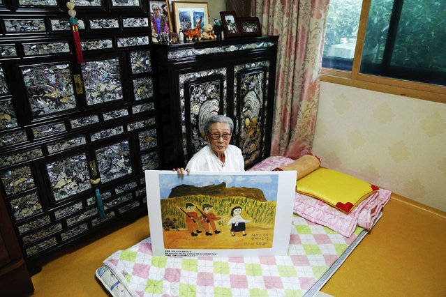 """Former South Korean """"comfort woman"""" Kim Bok-dong poses with a copy of her painting titled """"The Day A 14-year-old Girl Is Stolen Away"""" in her room at """"Our Home"""", a special shelter for former """"comfort women"""", in Seoul, South Korea, July 23, 2015. (Photo by Kim Kyung-Hoon/Reuters)"""