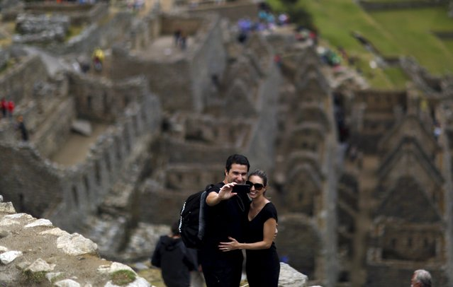 A couple takes a selfie at the Inca citadel of Machu Picchu in Cusco, Peru, August 12, 2015. (Photo by Pilar Olivares/Reuters)