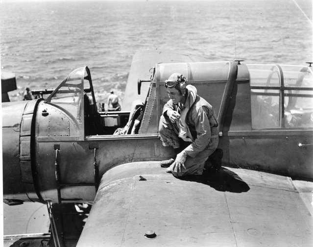 Back from mission over Guam (6-16-1944). Airdale Anderson laughs. near his hand note Jap shrapnel hole, which went through gas tank