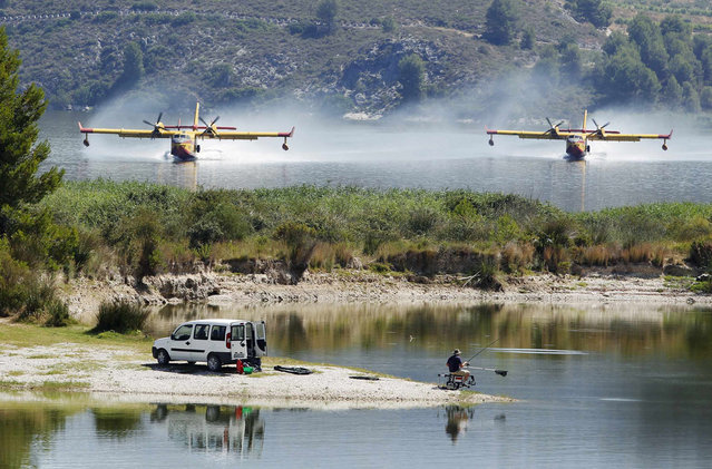 Firefighting planes fetch water from the Beniares reservoir to fight a wildfire next to the Sierra Mariola Nature Park in Cocentaina near Alicante, July 13, 2012