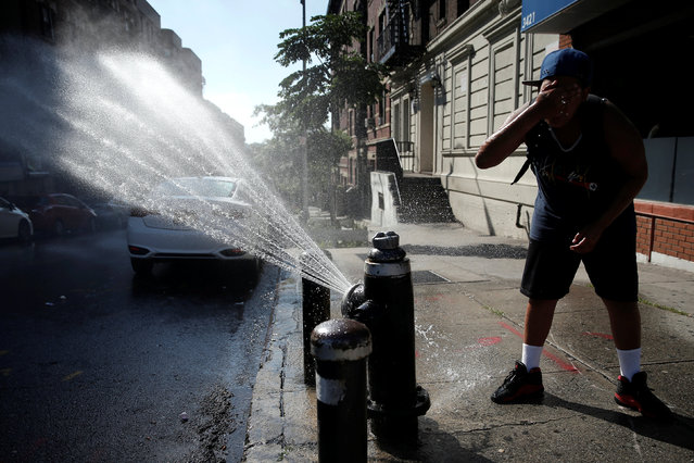 A boy cools off at an open fire hydrant on a hot day in the Washington Heights section of upper Manhattan, New York, U.S., July 6, 2016. (Photo by Mike Segar/Reuters)