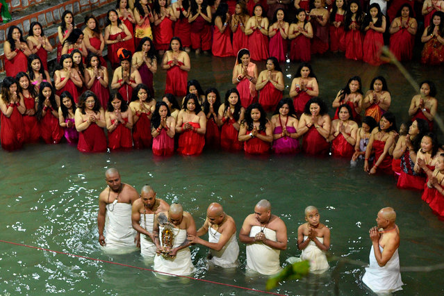 Hindu devotees perform rituals as they bathe in the Shali River on the outskirts of Kathmandu on January 10, 2020, to mark the Swasthani Brata Katha festival. Hundreds of married and unmarried women in the Himalayan nation have started a month-long fast for the Swasthani Brata Katha festival, marked with an auspicious bathing in water bodies in the hope of a prosperous life and conjugal happiness (Photo by Prakash Mathema/AFP Photo)
