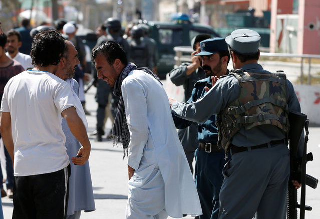 Afghan policemen try to comfort a man whose relatives were stuck at the site of a suicide attack followed by a clash between Afghan forces and insurgents after an attack on a Shi'ite Muslim mosque in Kabul, Afghanistan on Friday, August 25, 2017. (Photo by Omar Sobhani/Reuters)