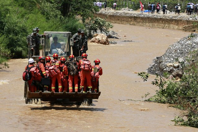 Rescue workers are transported into an earthquake zone on a front loader in Zhaotong, Yunnan province, August 5, 2014. A deadly earthquake hit Longtoushan town, Ludian county of Zhaotong on Sunday which has killed at least 410 people and injured 2,373, according to the state media. (Photo by Reuters/China Daily)