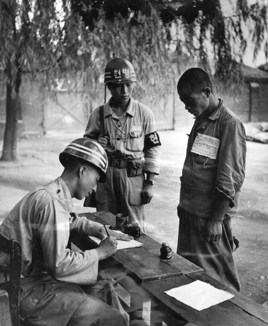 A North Korean prisoner of war being registered by a member of the South Korean forces at a POW camp at Taegu during the Korean War, 1950. (Photo by Bert Hardy)
