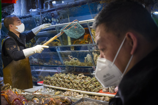 A customer wears a face mask as he shops for seafood at a market in Beijing, Saturday, March 14, 2020. The United States declared a state of emergency Friday as many European countries went on a war footing amid mounting deaths as the world mobilized to fight the widening coronavirus pandemic. For most people, the new coronavirus causes only mild or moderate symptoms, such as fever and cough. For some, especially older adults and people with existing health problems, it can cause more severe illness, including pneumonia. (Photo by Mark Schiefelbein/AP Photo)