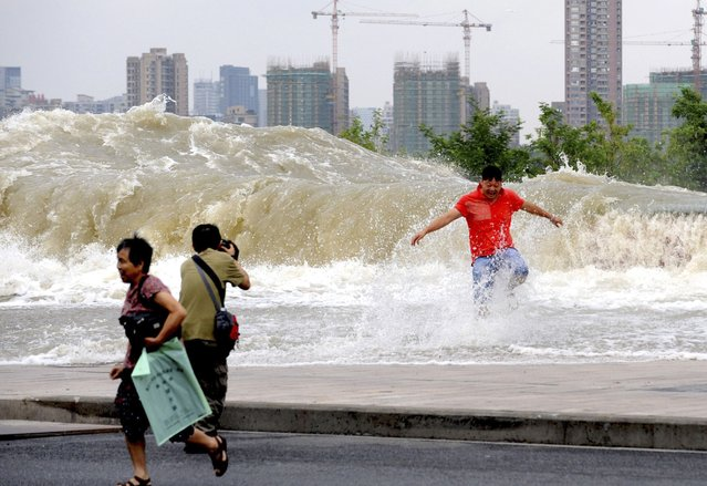 A man (2nd L) takes pictures as visitors run away from a wave caused by a tidal bore which surged past a barrier on the banks of Qiantang River, in Hangzhou, Zhejiang province August 14, 2014. (Photo by Reuters/Stringer)