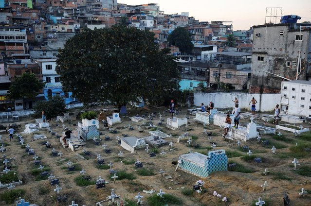 People fly kites in a cemetery in the Vila Operaria Favela of Rio de Janeiro, Brazil, July 10, 2016. (Photo by Nacho Doce/Reuters)