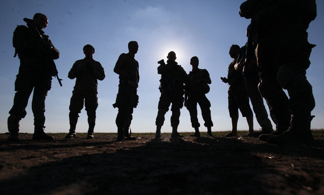 Ukrainian soldiers gather at a point close to Luhansk, eastern Ukraine, Wednesday, August 20, 2014.  Ukrainian troops made a significant push into rebel-held territory in eastern Ukraine, claiming control over a large part of Luhansk and encircling the largest rebel-held city, Donetsk, in fighting that has left at least 43 dead. (Photo by Petro Zadorozhnyy/AP Photo)