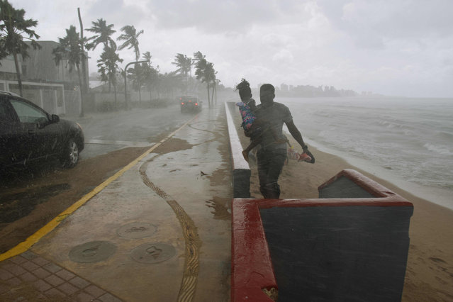 """A man and his daughter flee from the rain on a beach in San Juan, Puerto Rico, on September 19, 2017, prior to the arrival of Hurricane Maria. Maria headed towards the Virgin Islands and Puerto Rico  after battering the eastern Caribbean island of Dominica, with the US National Hurricane Center warning of a """"potentially catastrophic"""" impact. (Photo by Hector Retamal/AFP Photo)"""