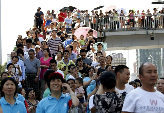 People watch military helicopters on a pedestrian overpass outside the closed area during the military parade to mark the 70th anniversary of the end of World War Two, in Beijing, China, September 3, 2015. (Photo by Kim Kyung-Hoon/Reuters)