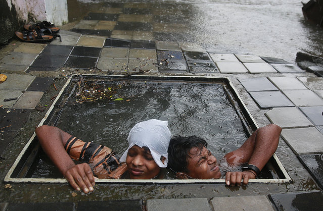 Municipal workers try to retrieve the lid of a manhole to prevent pedestrians from falling in, in Mumbai, India, Wednesday, September 20, 2017. Incessant rainfall in India's commercial capital has affected air and rail traffic, and schools and colleges remained shut for the day. (Photo by Rafiq Maqbool/AP Photo)