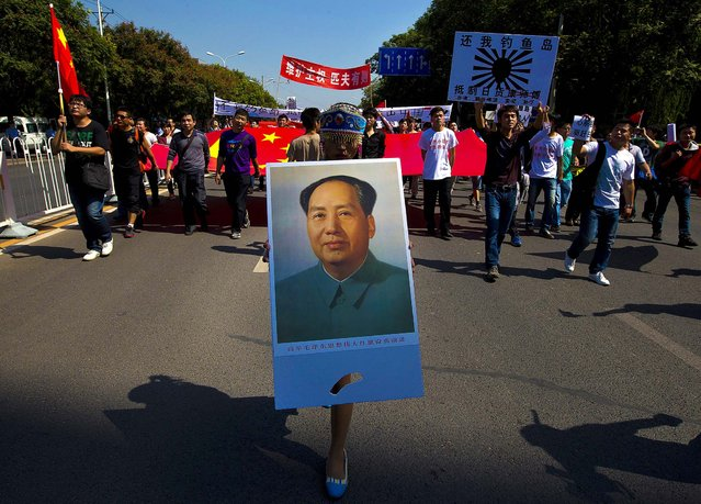 A demonstrator dressed in a traditional costume holds a picture of late Communist leader Mao Zedong during an anti-Japan protest outside the Japanese Embassy in Beijing September 16, 2012. (Photo by Andy Wong/Associated Press)