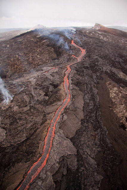 In this September 21, 2011 photo provided by the U.S. Geological Survey, lava flows from Kilauea volcano at Volcanoes National Park in Hawaii. Lava began flowing from the fissure breakout that started last week at Kilauea, a volcano that has been continuously erupting since 1983. It advanced about 2.3 miles before stopping short of the mostly abandoned Royal Gardens subdivision. (Photo by Tim Orr/AP Photo/USGS)
