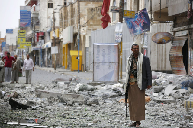 A Shiite fighter known as a Houthi stands guard in front of buildings destroyed by a Saudi-led airstrike in Sanaa, Yemen, Saturday, September 5, 2015. (Photo by Hani Mohammed/AP Photo)