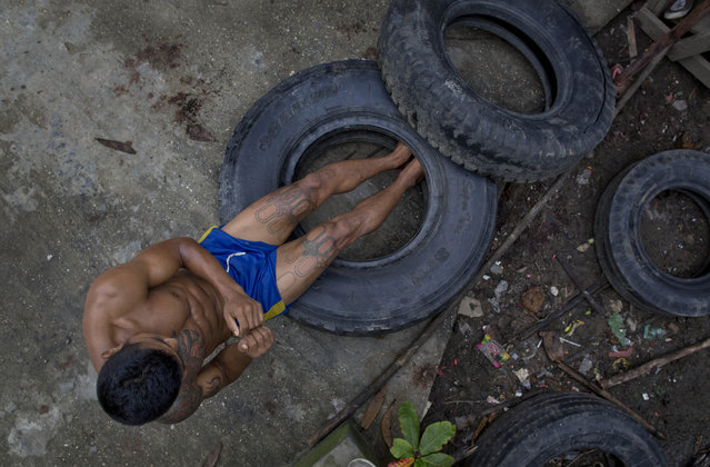 In this Wednesday, July 15, 2015, photo, a member of the White New Blood lethwei fighters club, a Myanmar traditional martial-arts club which practices a rough form of kickboxing, does crunches with the help of discarded tires in their gym on a street in Oakalarpa, north of Yangon, Myanmar. (Photo by Gemunu Amarasinghe/AP Photo)