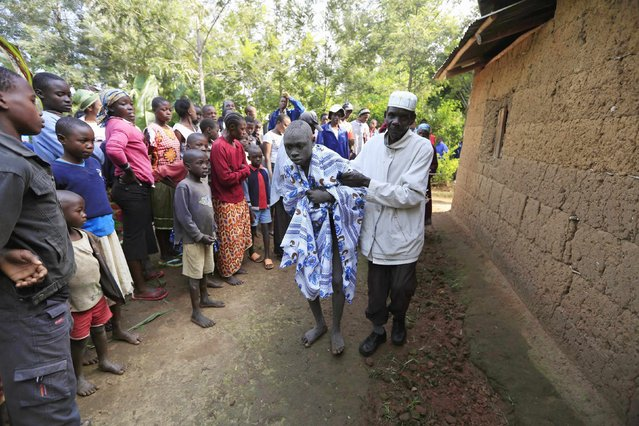 A Bukusu youth who just underwent circumcision is assisted by his father outside their home in Kenya's western region of Bungoma August 9, 2014. (Photo by Noor Khamis/Reuters)