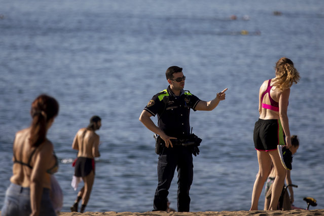 A police officer asks people to not sit while patrolling at the beach in Barcelona, Spain, Wednesday, May 20, 2020. Barcelona permitted Wednesday for people to walk on its beaches for the first time since the start of the coronavirus lockdown over two months ago. Sunbathing and recreational swimming are still not allowed. (Photo by Emilio Morenatti/AP Photo)