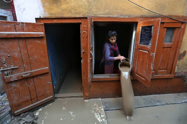 A Kashmiri woman drains muddy water  from her flood damaged house in Srinagar, Indian-controlled Kashmir, Thursday, September 18, 2014. The floods engulfed much of Kashmir two weeks ago, leaving hundreds of thousands of people homeless in both the Indian- and Pakistani-administered areas of the disputed territory. (Photo by Dar Yasin/AP Photo)