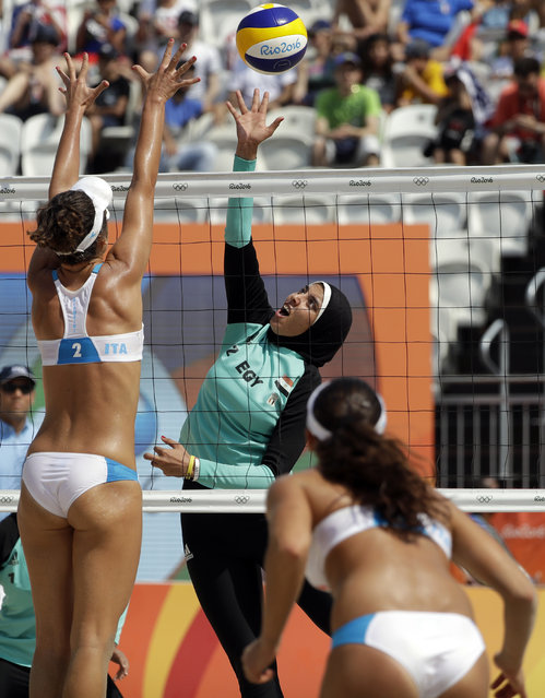 Egypt's Doaa Elghobashy, center, hits over Italy's Laura Giombini, left, during a women's beach volleyball match at the 2016 Summer Olympics in Rio de Janeiro, Brazil, Tuesday, August 9, 2016. (Photo by Marcio Jose Sanchez/AP Photo)
