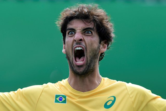 Brazil's Thomaz Bellucci celebrates after winning against Belgium's David Goffin during their men's singles third round tennis match at the Olympic Tennis Centre of the Rio 2016 Olympic Games in Rio de Janeiro on August 11, 2016. (Photo by Javier Soriano/AFP Photo)
