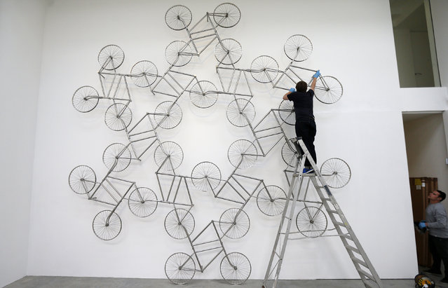 """A gallery technician assembles a sculpture made from stainless steel bicycles entitled """"Forever"""" by Ai Weiwei at the Lisson Gallery in London May 22, 2014. (Photo by Suzanne Plunkett/Reuters)"""