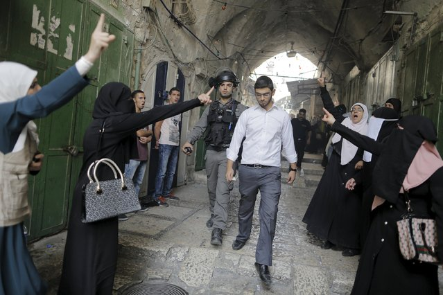 An Israeli policeman escorts an Israeli Jew as Palestinian women gesture in Jerusalem's Old City September 13, 2015, Israeli police raided the plaza outside Jerusalem's al-Aqsa mosque on Sunday in what they said was a bid to head off Palestinian attempts to disrupt visits by Jews and foreign tourists on the eve of the Jewish New Year. (Photo by Ammar Awad/Reuters)