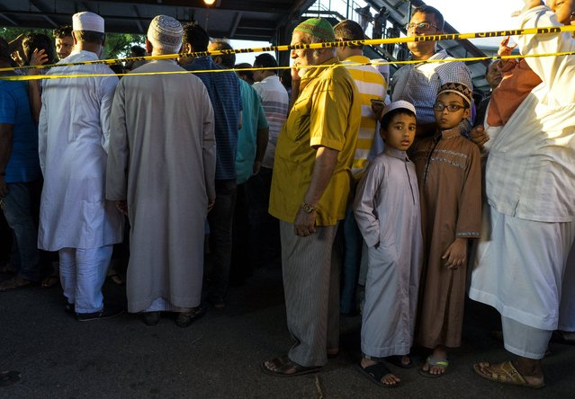 People gather for a demonstration Saturday, August 13, 2016, in the Queens borough of New York, near a crime scene after the leader of a New York City mosque and an associate were fatally shot as they left afternoon prayers. Police said 55-year-old Imam Maulama Akonjee and his 64-year-old associate, Tharam Uddin, were shot as they left the Al-Furqan Jame Masjid mosque. (Photo by Craig Ruttle/AP Photo)