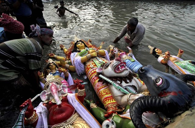 An idol of the Hindu Goddess Durga is immersed into the River Ganges in Kolkata, India October 24, 2012. (Photo by Bikas Das/Associated Press)