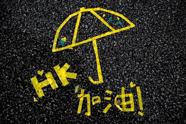 A message of support made with yellow tape is seen on a road near the Hong Kong government headquarters in Hong Kong on October 3, 2014. Students whose peaceful protests have paralysed parts of the global financial hub have agreed to hold talks with the government while vowing to continue their occupation, as the city's under-fire leader refused to stand down. (Photo by Philippe Lopez/AFP Photo)