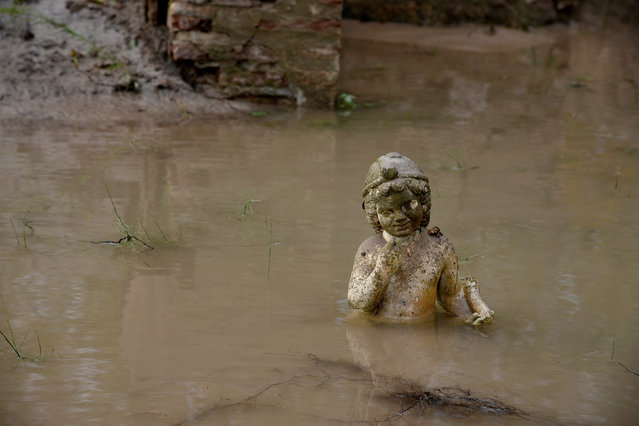 An ancient statue is partly submerged under water at an archaeological site, following flash floods which hit the area, at the village of Dion, Greece November 18, 2017. (Photo by Alexandros Avramidis/Reuters)