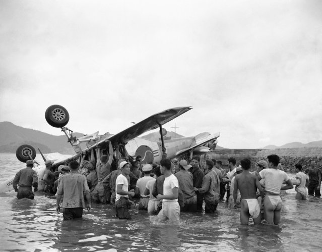 American and South Korean soldiers raise mustang fighter plane in attempt to keep trapped South Korean pilot's head above water after his plane skidded on takeoff van overturned off Yellow Sea Beach in Korea on September 16, 1950. Lt. Chong Yong Chin, American-trained flier, lost his life after receiving honor as first South Korean pilot to be chosen for mission over enemy territory. (Photo by Jim Pringle/AP Photo)