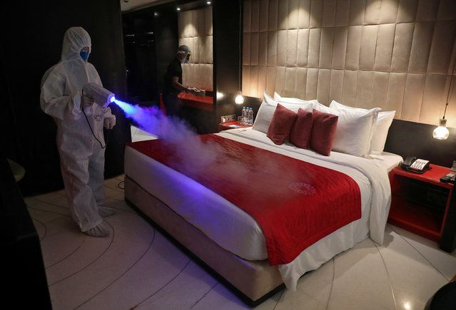 A worker wearing protective gear sanitizes a room at a hotel, after authorities eased lockdown restrictions that were imposed to slow the spread of the coronavirus disease (COVID-19), in Kolkata, India, June 15, 2020. (Photo by Rupak De Chowdhuri/Reuters)