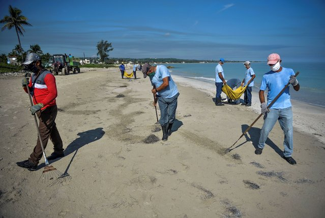 Workers wearing face masks clean the beach east of Havana on June 15, 2020 as Cuba prepares for a gradual reopening of the country amid the COVID-19 coronavirus pandemic. Cuba is planning to welcome tourists with COVID-19 tests and limit their contact with locals as part of a raft of measures designed to get its vital tourism industry back up and running. The government of President Miguel Diaz-Canel said it would gradually open up the economy in the next weeks, with a particular focus on recovering tourism dollars lost to the lockdown. (Photo by Yamil Lage/AFP Photo)