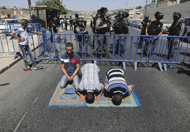 Palestinian men take part in Friday prayers outside the Old City as Israeli border police officers patrol nearby in Arab east Jerusalem neighbourhood of Ras al-Amud September 18, 2015. (Photo by Ammar Awad/Reuters)