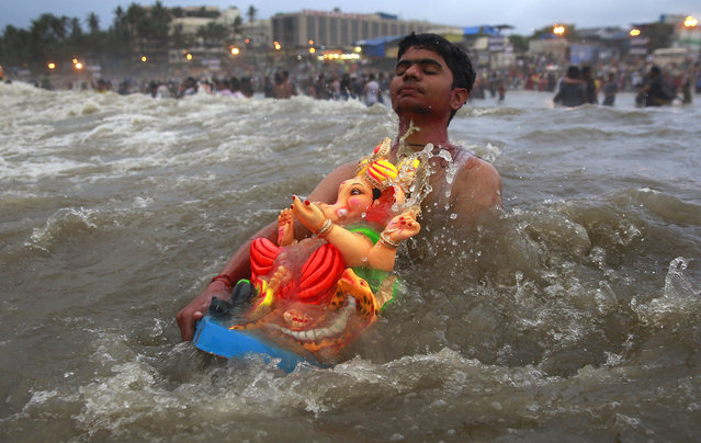 A devotee carries an idol of Hindu elephant headed god Ganesha to immerse it in the Arabian Sea during Ganesh Chaturthi festival celebrations in Mumbai, India, Monday, September 21, 2015. The festival is celebrated as the birthday of Ganesha, the Hindu god of wisdom, prosperity and good fortune. (Photo by Rafiq Maqbool/AP Photo)