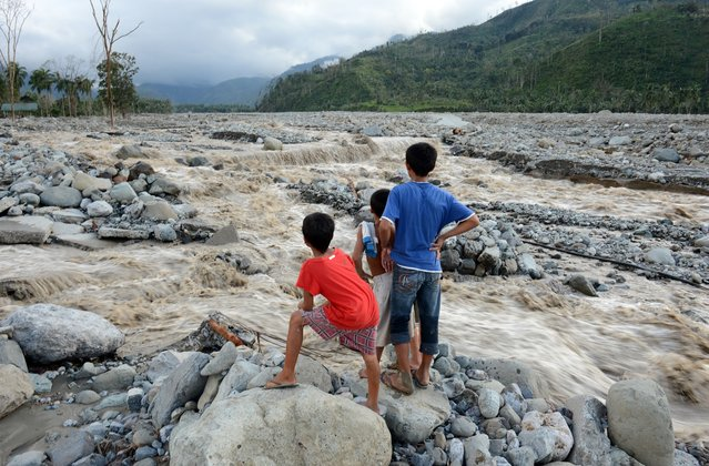 Children look at the a damaged road destroyed by flash floods at the height of Typhoon Bopha in the village of Andap, New Bataan town, Compostela Valley province, December 5, 2012. (Photo by Ted Aljibe)