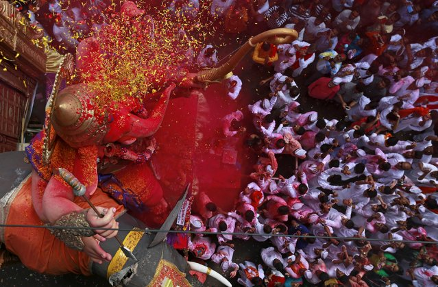 An idol of Hindu god Ganesh, the deity of prosperity, is showered with coloured powder and flowers as it is taken through a street on the last day of the ten-day-long Ganesh Chaturthi festival in Mumbai, India, September 27, 2015. (Photo by Danish Siddiqui/Reuters)