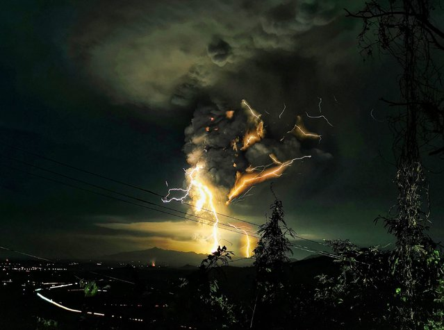 """Lightning streak over Batangas as Taal Volcano continue its eruption on Sunday evening, January 12, 2020 in the central Philippines. Phivolcs reminded the public that the volcano's main crater was """"strictly off limits"""" due to sudden steam explosions and the possible release of high concentrations of lethal volcanic gases. Residents of towns near Taal Volcano are being taken to safer ground following increasing volcanic activity, a disaster-mitigation official said. (Photo by Domcar C. Lagto/SIPA Press/Pacific Press/Rex Features/Shutterstock)"""