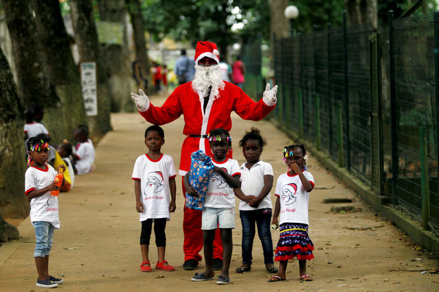 A man dressed as Santa Claus gestures as he poses with children during a visit at the zoo of Abidjan, Ivory Coast December 21, 2017. (Photo by Luc Gnago/Reuters)