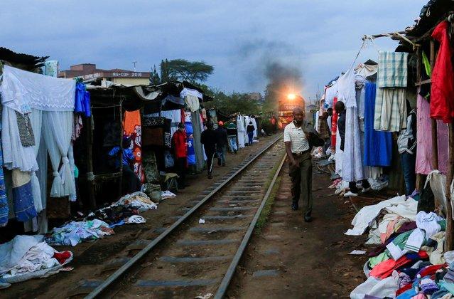 A man walks along a railway line as a commuter train approaches, amid the spread of the coronavirus disease (COVID-19), at the Kibera slums, in Nairobi, Kenya on July 6, 2020. (Photo by Thomas Mukoya/Reuters)