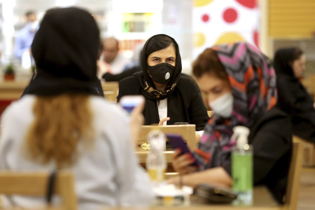 Women wearing protective face masks to help prevent spread of the coronavirus sit at a shopping center food court, in Tehran, Iran, Wednesday, August 19, 2020. Iran surpassed 20,000 confirmed deaths from the coronavirus on Wednesday, the health ministry said — the highest death toll for any Middle East country so far in the pandemic. (Photo by Ebrahim Noroozi/AP Photo)