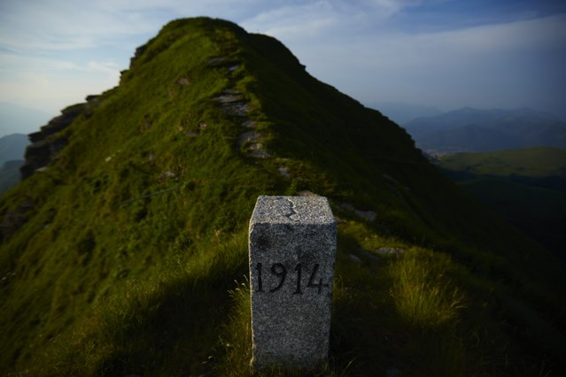 A marker stands on a ridge dividing Switzerland (L) and Italy (R) at the Monte Generoso near Mendrisio May 11, 2014. (Photo by Denis Balibouse/Reuters)