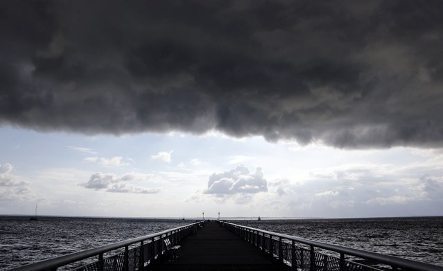 Dark clouds fill the Autumn sky over the jetty in Andernos, southwestern France, November 4, 2014. (Photo by Regis Duvignau/Reuters)